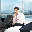 Young business man talking on phone sitting on bed in hotel room