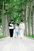 Senior man and woman holding boy´s hands while walking in the park