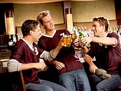 Three young men toasting with beer at bar counter
