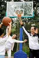 Boy playing basketball with senior man and woman