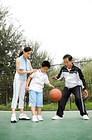 Boy dribbling basketball, woman and senior man watching