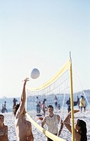 People playing beach volleyball on beach
