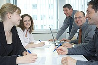Side profile of businessmen and businesswomen smiling in meeting
