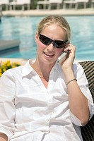 Woman 35 talking on the cell poolside