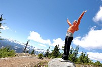Teen girl with arms open over mountains, Vancouver Island, B C