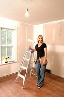 Woman holding paint roller, for home renovations