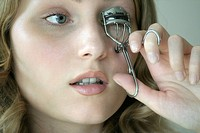 Close_up of young woman using eyelash curler