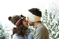 Young couple in winter clothes, kissing, side view