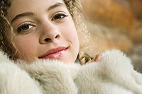 Teen girl under furry blanket, smiling at camera, close-up