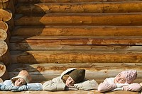 Three preteen or teen girls standing on deck of log cabin, resting heads on railing