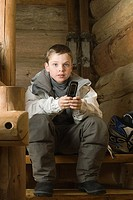 Boy dressed in ski clothes holding cell phone