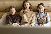 Teen girl and younger boy and girl watching TV together, front view