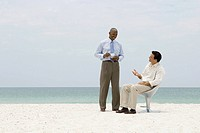 Two business associates chatting on beach, one holding coffee cup