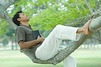 Man resting on tree branch with eyes closed, holding book