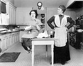 Housekeeper in the kitchen glaring at a young woman eating a cake All persons depicted are not longer living and no estate exists Supplier warranties ...