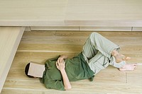 Boy lying on floor with book over face