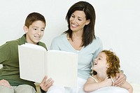 Mother reading book to son and daughter