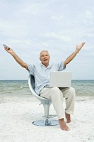 Senior man sitting on beach with laptop on lap, arms raised, shouting