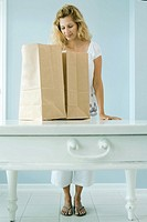 Woman looking into grocery bag (thumbnail)