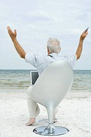 Senior man sitting in chair on beach, using laptop, arms in air, rear view