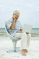 Senior man using cell phone and laptop, sitting in chair on beach