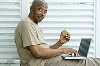 Senior man making credit card purchase online, smiling at camera
