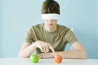 Teen boy wearing blindfold, pointing to red apple