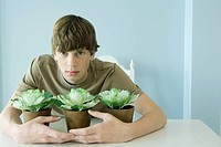 Teen boy protecting potted plants, looking at camera