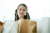 Little girl smiling, shopping bags in foreground