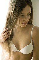 Young woman in bra holding hair in hand, looking away