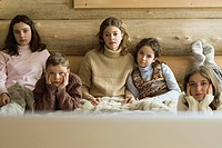 Group of teen and preteen friends and siblings watching TV, front view