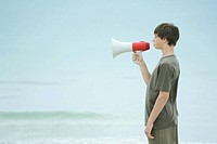 Boy using megaphone, side view