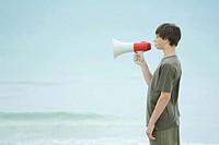 Boy using megaphone, side view