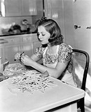 Young woman sitting on a chair and cutting beans All persons depicted are not longer living and no estate exists Supplier warranties that there will b...