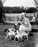 Woman feeding her dog and puppies All persons depicted are not longer living and no estate exists Supplier warranties that there will be no model rele...