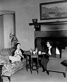Two women drinking tea and talking All persons depicted are not longer living and no estate exists Supplier warranties that there will be no model rel...