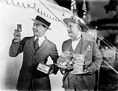 Man holding plates of sandwiches with a man looking at a film slide beside him All persons depicted are not longer living and no estate exists Supplie...