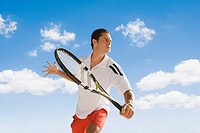 Man leaping holding tennis racket