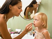 Mother and daughter applying makeup