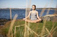 Young Woman doing Yoga on grass by sea