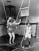 Female gymnast training with safety ropes with coach All persons depicted are not longer living and no estate exists Supplier warranties that there wi...