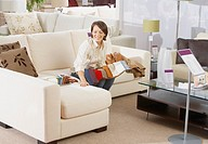 Woman sitting on sofa in furniture store