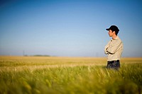Farmer standing in field of wheat, Saskatchewan, Canada
