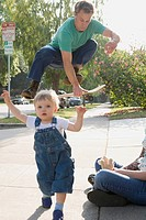 Man jumping on skateboard with toddler
