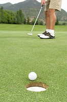 Golfer with golf ball at hole