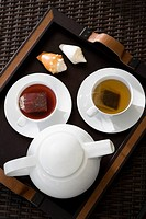 High angle view of cups of herbal tea with a teapot on a serving tray