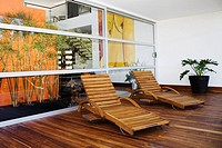 Two lounge chairs in a patio of a house