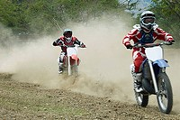 Two motocross riders riding motorcycles
