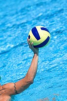 Close-up of a person's hand holding a water polo ball in a swimming pool