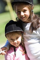 Close-up of two girls wearing riding hats and smiling